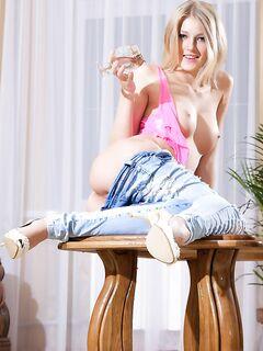 Сексуальная блондинка в джинсах раздевается на столе - секс порно фото