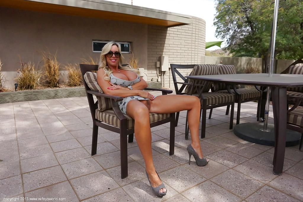 Грудастая зрелка разгуливает по двору топлес - секс порно фото
