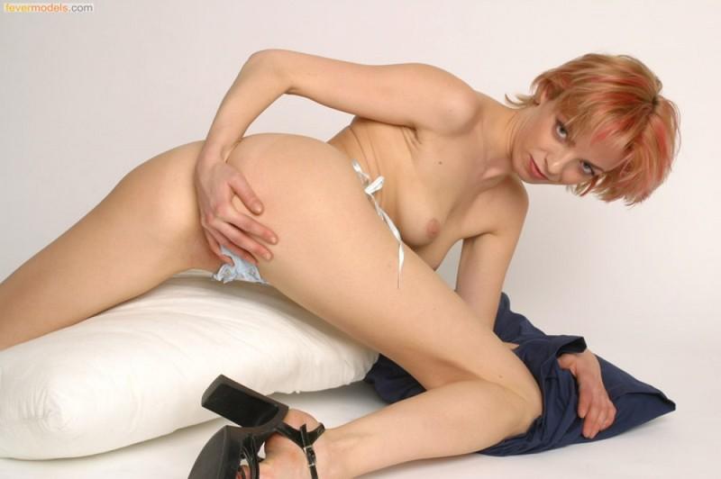 Рыжая девушка с маленькими сиськами позирует в стрингах - секс порно фото