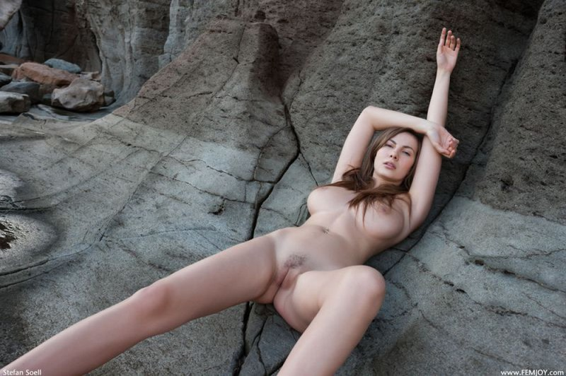 Эромодель с большой натуральной грудью позирует в скалах оголив - секс порно фото