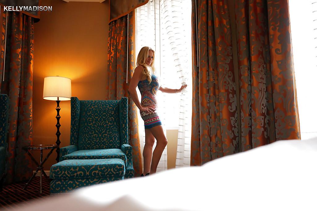 Грудастая блондинка раздевается в кресле гостиной - секс порно фото